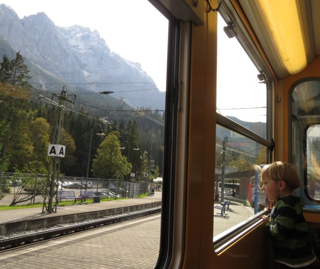 Logan on the cog train, with the snow-plastered Zugspitze looming out the window.