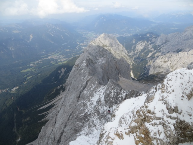 The view down the north face. Garmisch is at the top, center. The lower cable car station is visible on the far left (follow the line formed by the two red and white cable towers), and a red gondola is visible at lower center.
