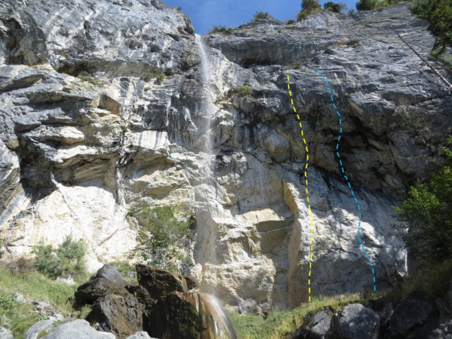 """Kate standing below Alex Huber's two most significant routes, Weisse Rose (L, in yellow) and Open Air (R, in blue). Originally given .14c and .14d (respectively) by Alex, Adam Ondra suggested an upgrade to .14d and .15a when he repeated them in 2008, to align with the """"new school"""" grading. In Ondra's words: """"Now when Action Directe is 9a, Open Air should be 9a+."""""""